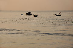 Fishing vessels on the sea at sunrise, Mui Ne, Vietnam Royalty Free Stock Photos