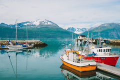 Fishing village and boats in Skibotn Norway. A beautiful scene of mountains, the ocean and some fishing boats in Skibotn, a fishing village in Norway Royalty Free Stock Images