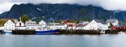 Fishing village on Lofoten in cloudy weather. Fishing village on Lofoten islands, Norway. Steep, high hills on the background are partially covered in clouds. A Royalty Free Stock Photography