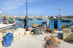 The fishing village of Marsaxlokk on Malta island. Marsaxlokk, Malta - 3 November 2017: fishermen preparing the fishing nets near their boat at Marsaxlokk on Stock Image
