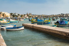 Fishing village Marsaxlokk, Malta. Traditional fishing village Marsaxlokk at the island Malta. Many colorful wooden boats in the bay. Church in the background Stock Photography