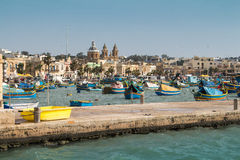 Fishing village Marsaxlokk, Malta. Traditional fishing village Marsaxlokk at the island Malta. Many colorful wooden boats in the bay. Church in the background Stock Image