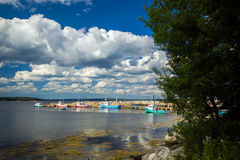 Fishing village, Nova Scotia. Wide angle view of a picturesque,summer landscape of colorful fishing boats tied up at a wharf along the Atlantic coast of  the Stock Photos