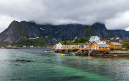 Fishing village with oragne houses on Lofoten in cloudy weather. Fishing village with orange houses on Lofoten in cloudy weather. High, steep mountains partially Stock Photography