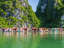 Fishing village reflected in emerald waters of Ha Long bay, Vietnam Stock Photography
