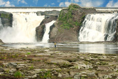 Fishing at the waterfall. Men ficshing near a big waterfall stock image