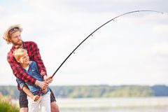 Fishing on weekend. Little boy and his father holding fishing rod over lake while spending summer weekend in natural environment stock photography