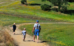 2 boys walking with Grandfather in nature. Two young boys and grandpa walking on a dirt road with fishing poles Royalty Free Stock Images