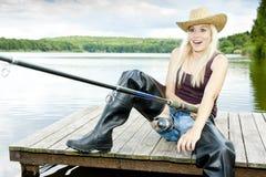 Fishing woman. Sitting on pier stock image