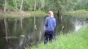 Fishing woman. Village pond bounces ripples from the rain on the surface of the water near the shore fishing woman stock footage
