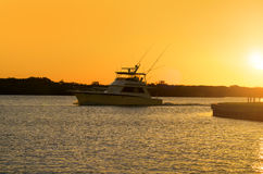 Fishing yacht leaving bay at sunrise to catch fish Stock Photo