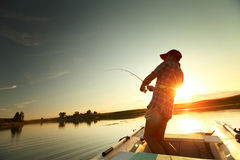 Fishing. Young man fishing from a boat at sunset Royalty Free Stock Images