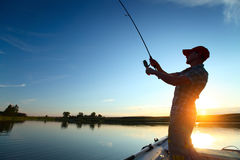 Fishing. Young man fishing from a boat at sunset Royalty Free Stock Photo