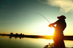 Fishing. Young man fishing on a lake from the boat at sunset Royalty Free Stock Image