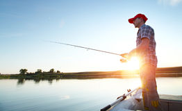 Fishing. Young man fishing on a lake from the boat at sunset Stock Images