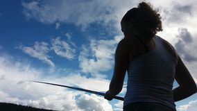 Fishing. A young woman angling under beautiful sky royalty free stock images