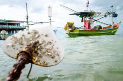 Fishingboat and anchor. Boat anchor and fishingboat floating in the sea Stock Photo