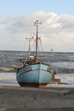 Fishingboat on the beach. A fishing-boat is lying on a sandy beach Stock Image