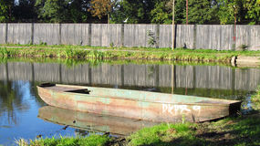 Fishingboat on the lake. Old fishingboat at the bank of the pond Stock Photography