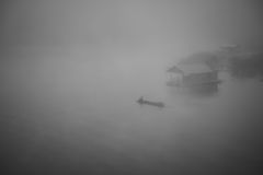 Fishingman on boat in a mystic foggy lake at morning Royalty Free Stock Photos