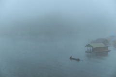 Fishingman on boat in a mystic foggy lake at morning Royalty Free Stock Image