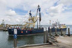 Fishingship entering harbour Stock Photo