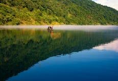 Fishman бросило сеть на шлюпке в тумане на реке, золотое отражение блеска солнца на поверхности воды стоковое фото rf
