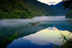Fishman на шлюпке в тумане на реке, золотое отражение облака на поверхности воды стоковые фотографии rf