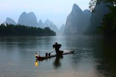 Fishman no alvorecer de Lijiang River foto de stock