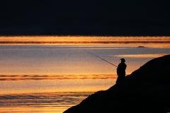 Fishman y puesta del sol Fotos de archivo