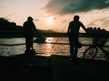 Fishmen de coucher du soleil Photographie stock
