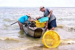 Fishmen pickup fish from boat Stock Photography