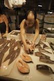 Fishmonger βάζει τις λωρίδες ψαριών στην αντίθετη αγορά ψαριών μέσα Στοκ Εικόνες