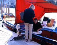 Fishmonger on boat, Venice. Royalty Free Stock Photo