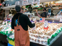 Fishmonger catches Dungeness crab at public market, Seattle. Workers at Fish Market toss crab over teeming display of dungeness crabs, Seattle Public Market royalty free stock image