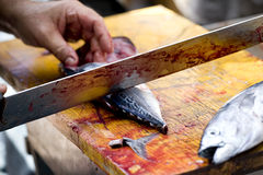 Fishmonger cutting fish. At a market stock images