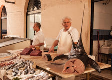 Fishmonger selling swordfish  in an old local market Royalty Free Stock Photos