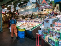 Fishmonger smiles for the camera in front of Pike Place Fish Co. Royalty Free Stock Images