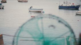 Fishnet cage and a small fishermans boat on the beach close-up on stock video footage