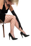 Fishnet covered legs. Black gloved hand on fishnet covered leg on a white background Royalty Free Stock Photos