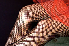 Fishnet detail. Close up of woman's legs wearing fishnet stockings. Enhanced with blue and red colored strobes to add unique color Royalty Free Stock Photo