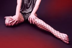 Fishnet Stockings. A long pair of legs covered in fishnet stockings stretches out from beneath a short dress Stock Photography