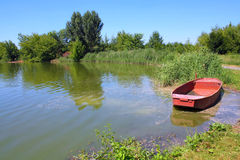 Fishpond with red boat Royalty Free Stock Image