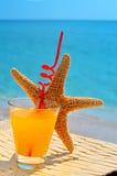 Fishstar exponeringsglas av den orange coctailen mot havet Royaltyfria Foton