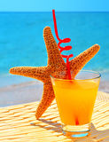 Fishstar, glass of orange cocktail against  blue sea Royalty Free Stock Image