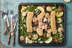 Fishsticks, garnalen en groenten op het bakindienblad stock foto