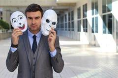 Fishy businessman holding scary masks isolated.  royalty free stock photo