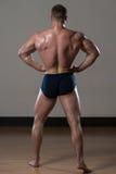 Fisicamente uomo che mostra la sua parte posteriore ben preparata fotografie stock
