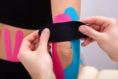 Fisioterapeuta Applying Kinesiology Tape en el codo del paciente fotos de archivo libres de regalías