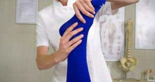 Fisioterapeuta de sexo femenino que da masaje del pie a un paciente metrajes